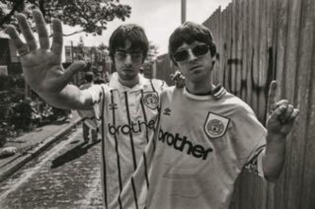 Liam and Noel Gallagher wearing Manchester City football shirts