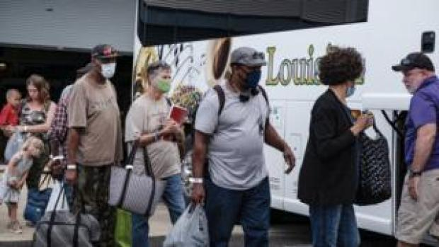 People board a bus during evacuations in Lake Charles, Louisiana