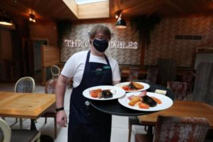 A waiter wearing a face mask carries a tray of three breakfasts