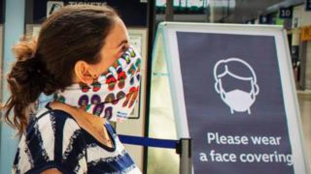 Woman at railway station wearing a face mask