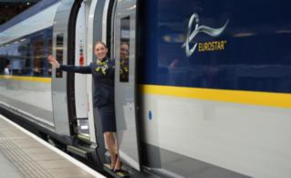 A Eurostar staff member waving from the new e320 train