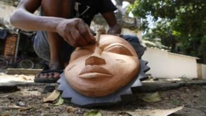 A sculptor carves a mask in his sculpture workshop in Grand-Bassam, Ivory Coast