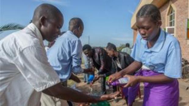 Parishioners wash hands as a preventive measure against the spread of the COVID-19 coronavirus