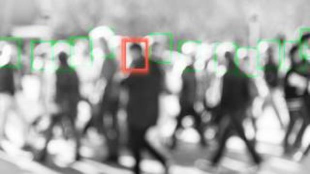 A blurred man is singled out of a crowd by a tracking square in this photo illustration