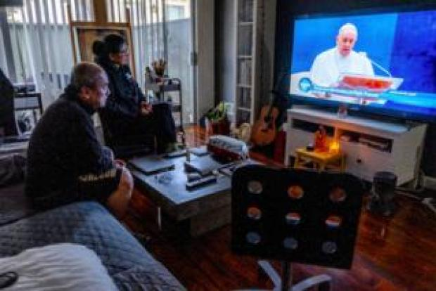 Miguel's family watches the Pope give a blessing on TV