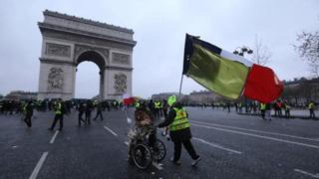 "A demonstrator in a wheelchair is pushed by another, holding a French national flag with a yellow one attached to it, with the Arc de triomphe in the background during a Yellow Vests ""Gilets Jaunes"" anti-government demonstration in Paris on 12 January 2019"