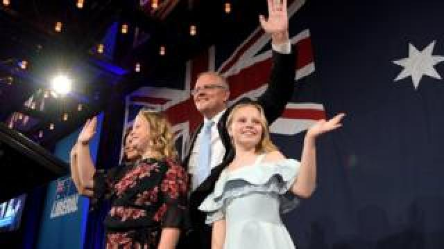 Scott Morrison and his children wave to supporters at his victory party
