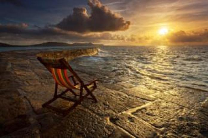 Deckchair on the beach at sunrise