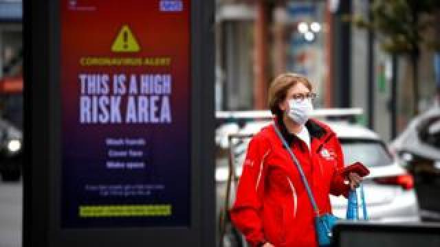 A woman wearing a protective mask walks past a warning sign in Manchester, as the city and the surrounding area faces local restrictions in an effort to avoid a local lockdown being forced upon the area, amid the coronavirus disease