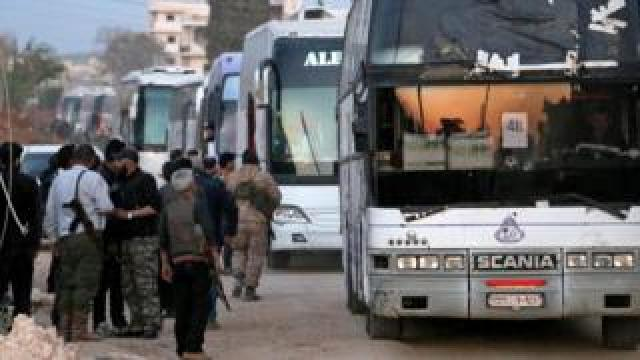 Syrian rebel fighters stand guard as buses bringing a new batch of evacuees from Waer, the last opposition-held district of Syria's third city Homs, arrive in the city of al-Bab in the northern Aleppo province