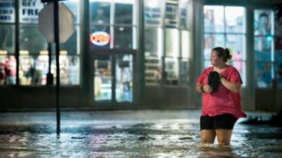 A woman walks through floodwaters in Myrtle Beach, South Carolina on 3 August