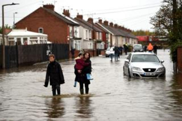 Residents walk through flood water