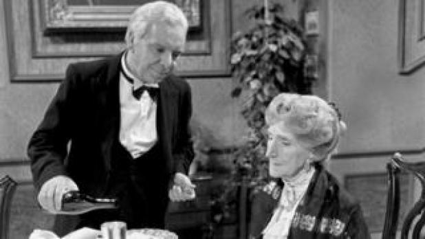 A black and white still from Dinner for one shows James the butler pour drinks for Miss Sophie