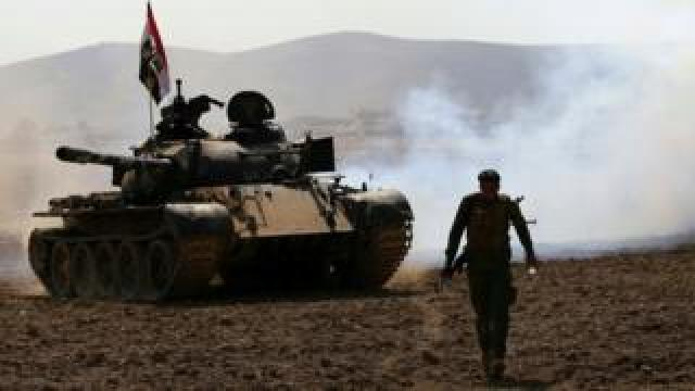 Iraqi government forces advance in the village of Badoush, some 15km northwest of Mosul, during the battle to retake the city's west from so-called Islamic State (IS), 8 March 2017