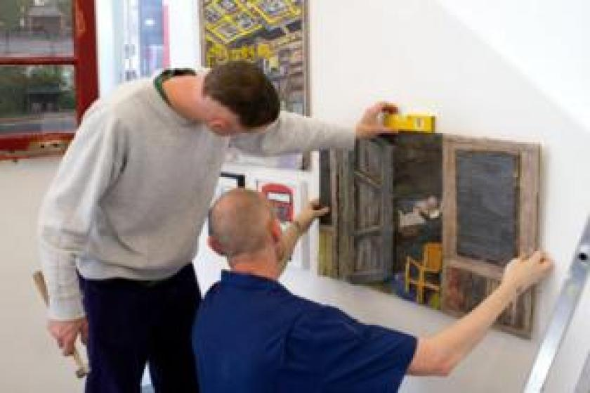 Two men hang artwork on a wall