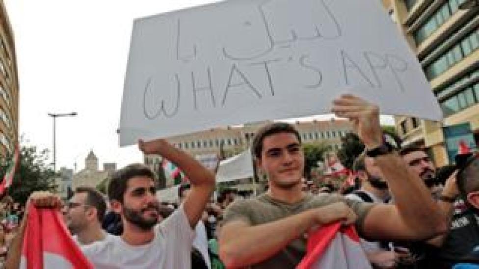 """أحد المتظاهرين يحمل لافتة كُتب عليها """"لبيك يا واتساب"""""""
