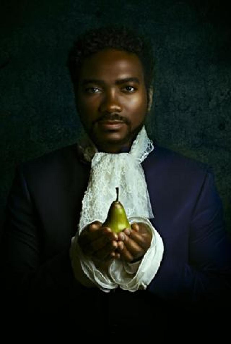 Portrait by Alanna Airitam showing a man holding a pear