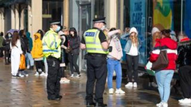 Police officers patrol as customers queue outside the Primark store on Princes Street in Edinburgh on June 29, 2020 as part of Scotland's phased plan to ease out of the coronavirus pandemic lockdown. - Parks, markets and shops with outdoor entrances reopened across Scotland