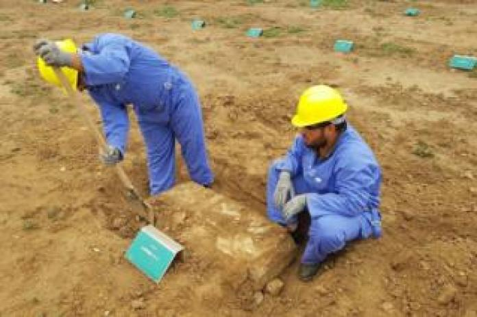 Two men wearing blue suits and yellow helmets to restore graves in Iraq