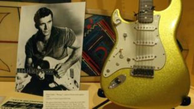 A photo of Dick Dale alongside his custom Fender Stratocaster guitar on display at an exhibit at the Fullerton Museum Center, California