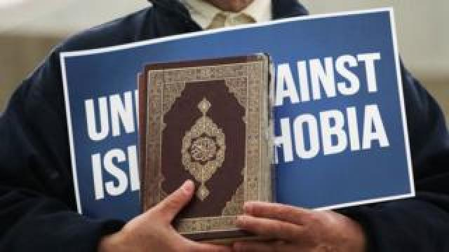 Person carrying 'unite against Islamophobia' sign and a Koran