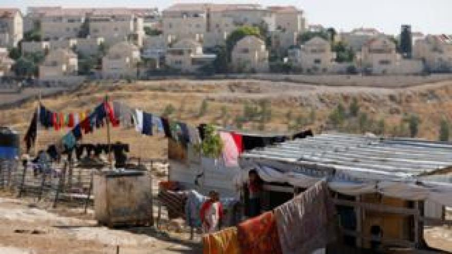 File photo showing Palestinian children play outside their dwelling in al-Eizariya, near the Jewish settlement of Maale Admumim in the occupied West Bank (20 July 2019)