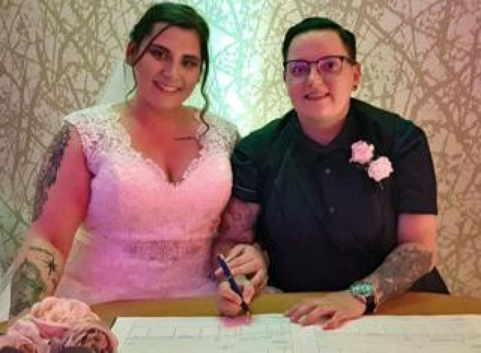 A wedding couple signs their marriage certificate