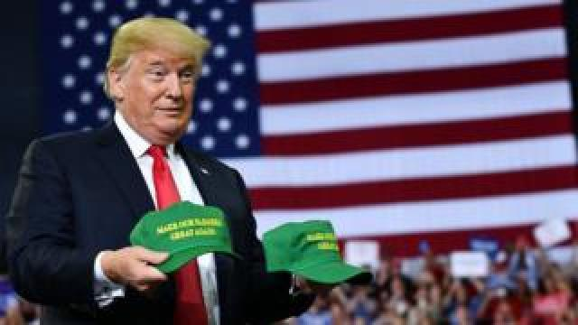 "US President Donald Trump displays hats that read: ""Make Our Farmers Great Again!"" at a campaign rally at Ford Center in Evansville, Indiana on August 30, 2018"