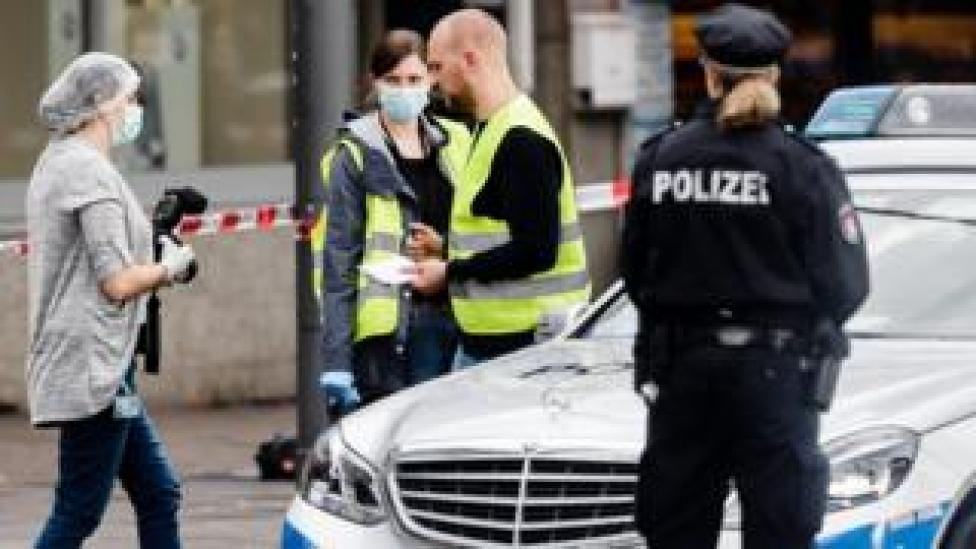 Police investigators search for evidence at the area around a supermarket in the northern German city of Hamburg, where a man killed one person and wounded several others in a knife attack, 28 July 2017