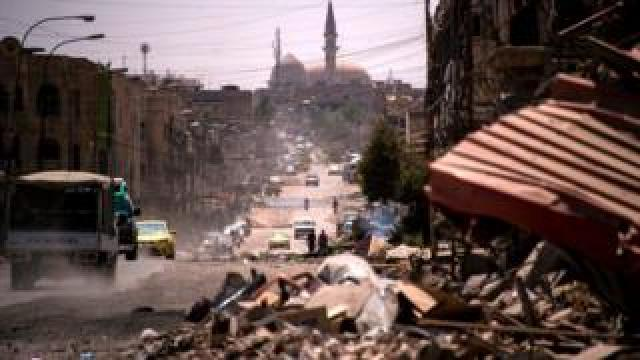 Cars drive along a damaged street in western Mosul on 12 July 2017