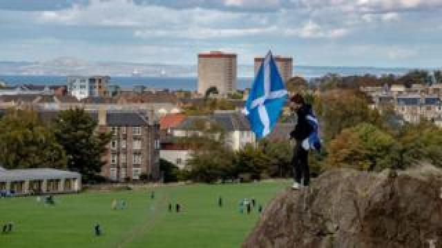 A man holding Saltire with a view over Edinburgh