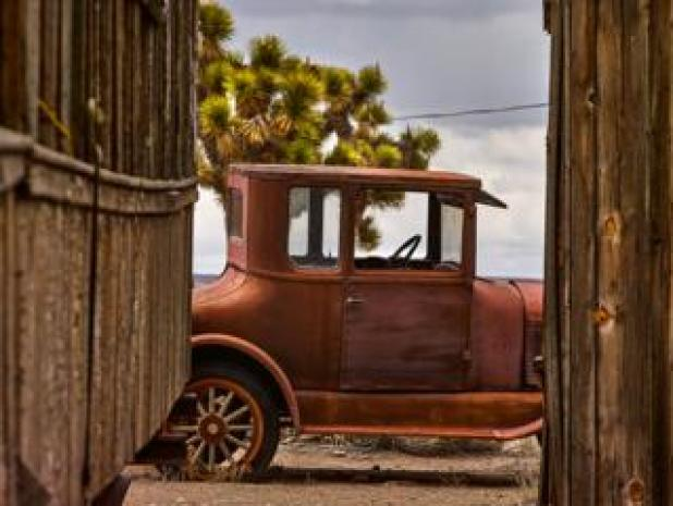 Cars: An abandoned car seen between two wooden buildings