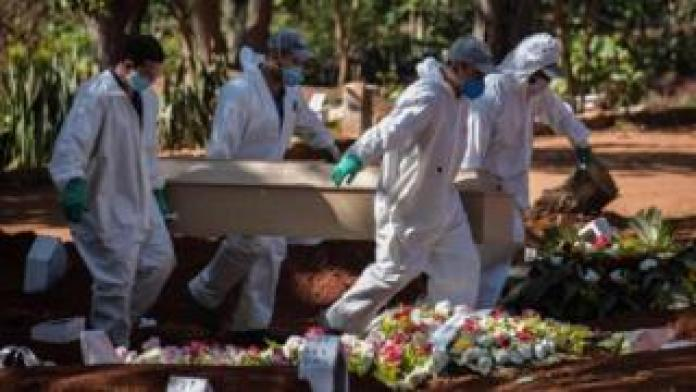 Employees carry the coffin of a deceased Covid-19 in Sao Paulo, Brazil