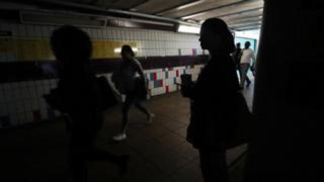 People walking in darkness in the passenger tunnel under Clapham Junction station