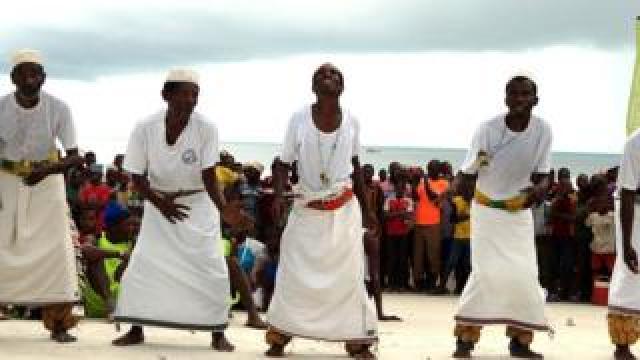 Alongside, men wearing white kikoi dance to entertain those who turned out at the finish line