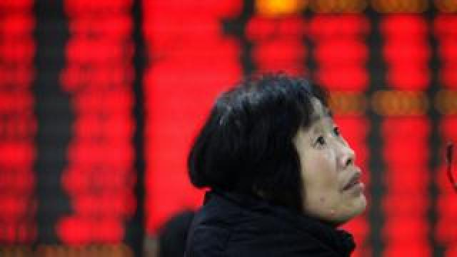 A woman watchs the eclectric monitor at A STOCK EXCHANGE in Huaibei March 9th , 2015