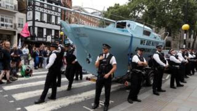 Police stand in front of a boat used by climate change protesters to block a road in London