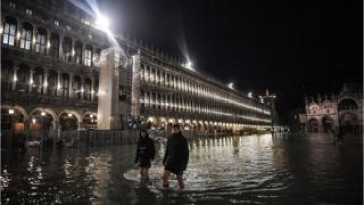 People wade through water in St Mark's Square