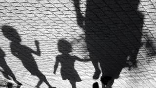 Blurry shadow of a little boy and a girl walking with adults in black and white