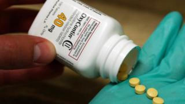 Tablets dispensed from a bottle of OxyContin into a gloved hand