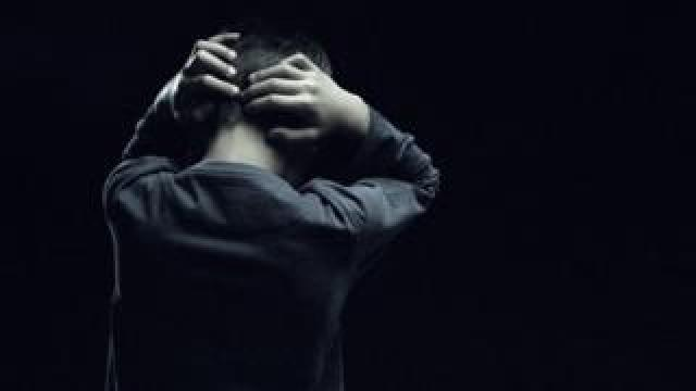 Boy with hands on back of his head
