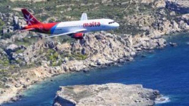 Air Malta passenger jet flying over coastline