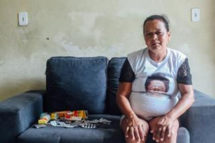 Josilene Batista sentada no sofá da casa do filho