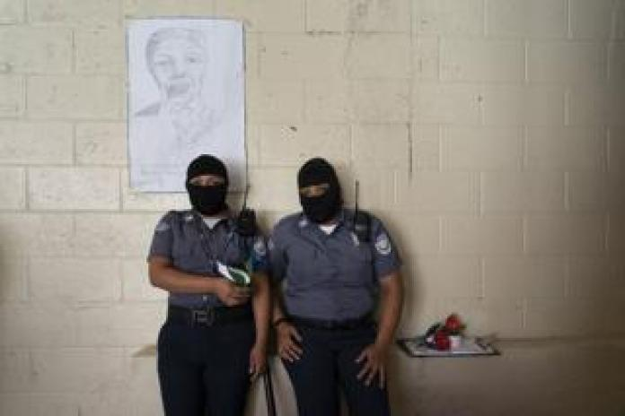 Prison guards, wearing hoods to protect their identity, stand in front of a portrait of Nelson Mandela at the Penal Center in Quezaltepeque, El Salvador. November 9, 2018.