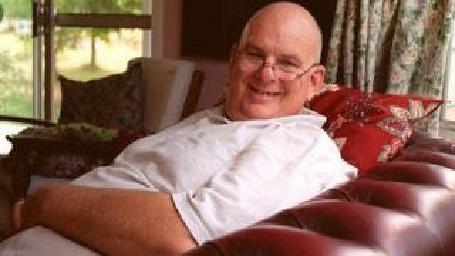 Les Murray sat in a living room on a leather sofa, reclined, smiling