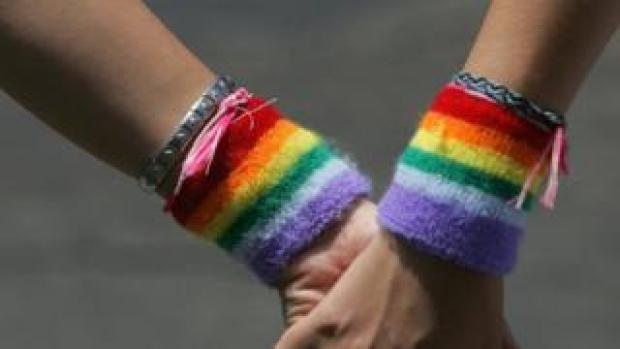 a lesbian couple wearing rainbow wristbands hold hands