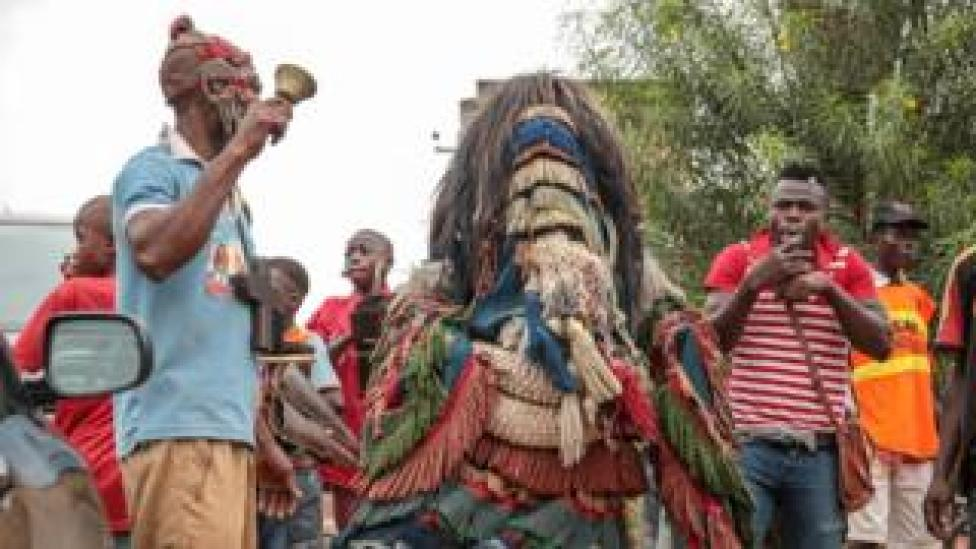 Man in a traditional masquerade costume along with a bell ringer in the streets of Arondizuogu during the Ikeji Festival in Nigeria