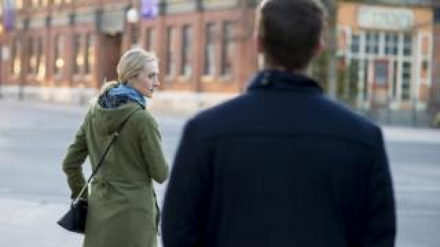 Stock photo of woman looking over her shoulder at a stranger