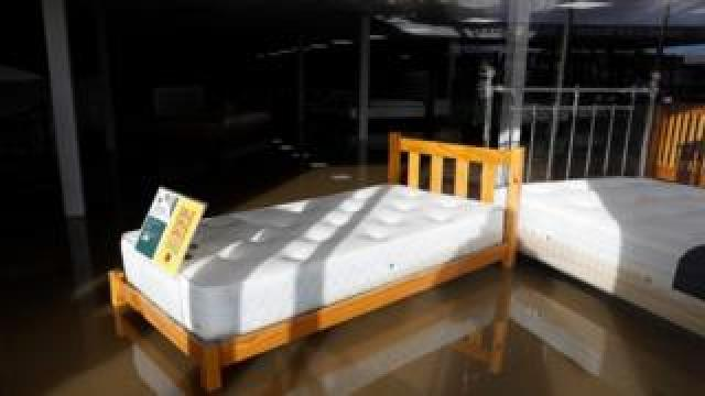 A bed in the window of a shop stands in floodwater