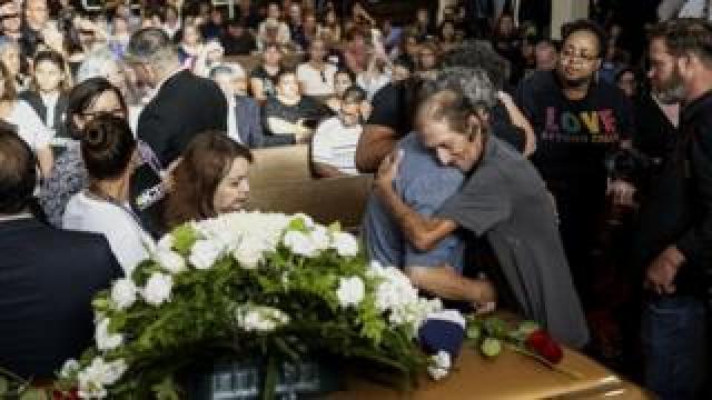 Antonio Basco in front of his wife's casket
